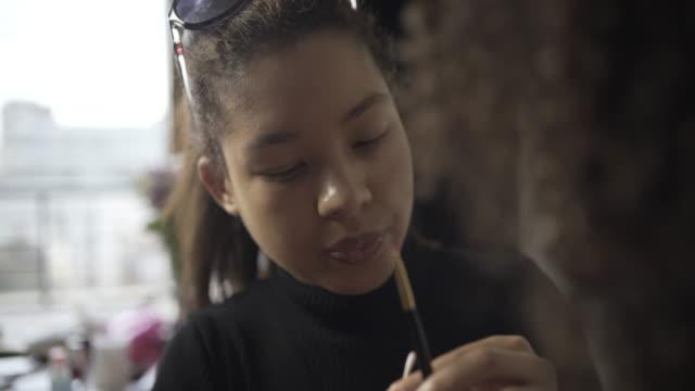 A make-up artist applying lip colour.