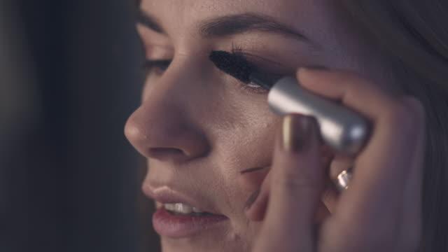 Makeup artist applying mascara on eyelashes with makeup brush