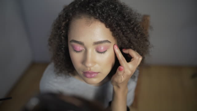 A make-up artist applying pink eyeshadow.
