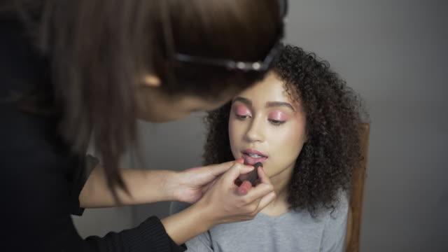 A make-up artist applying pink lipstick.