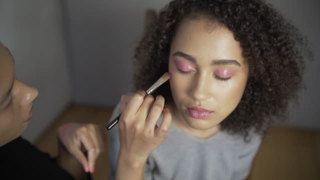 A make-up artist applying Pink rouge