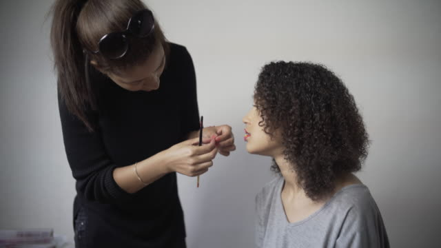 A make-up artist applying tiny real flowers to the lips of a model.