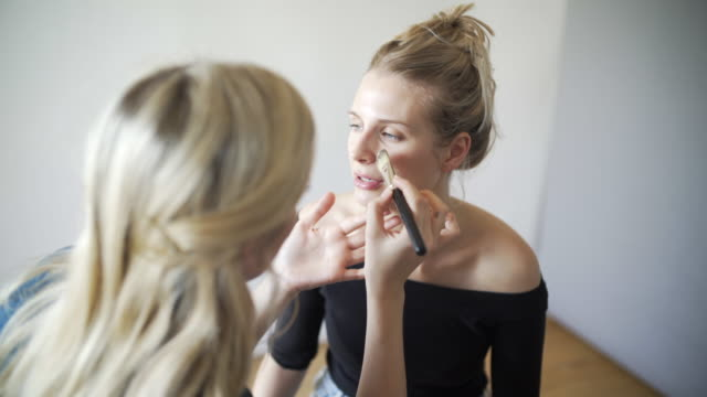 A make-up artist at work behind the scenes, creating a modern make-up look.