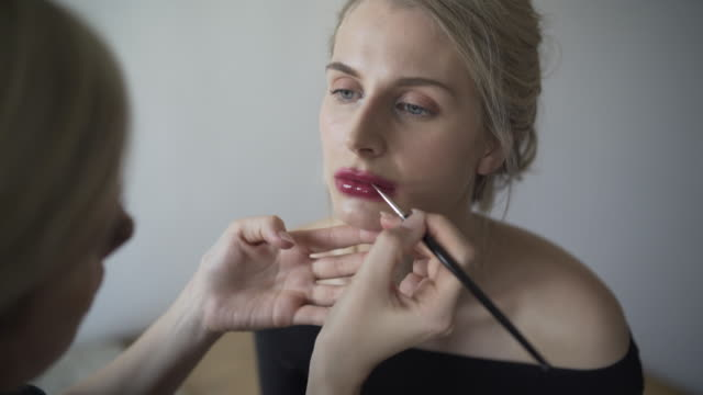 A make-up artist at work behind the scenes, creating the snogged lip, smudged lipstick trend.