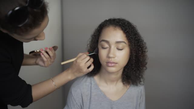 A make-up artist blending foundation.