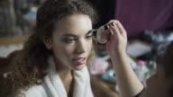 A make-up artist brushing a models eyebrows.