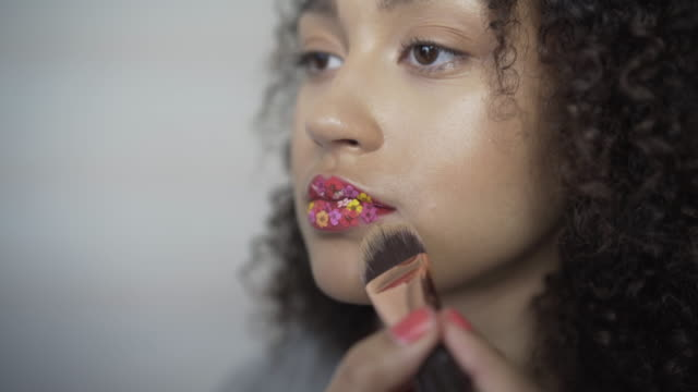 A make-up artist brushing down and finishing of the lips covered with tiny flowers.