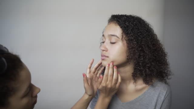 A make-up artist massaging a models face.