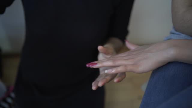 A make-up artist painting a models nails.