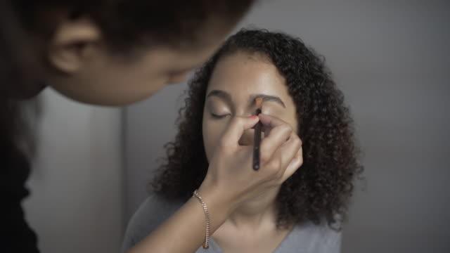 A make-up artist using an eyebrow brush