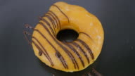 making dark chocolate stripes on donut . close up.