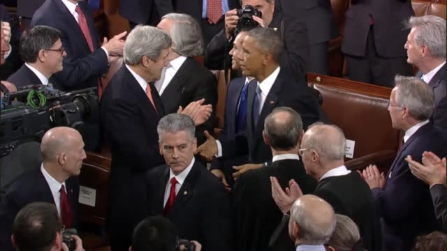 Making his way to the dais the President shakes hands with administration officials judges from nation's High Court