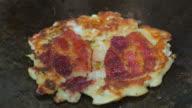 Making okonomiyaki on teppanyaki pan. Front view.