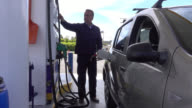 Male adult stopping at gas station to refuel his car