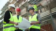 Male and female architect presenting plan details to the male investor at the construction site