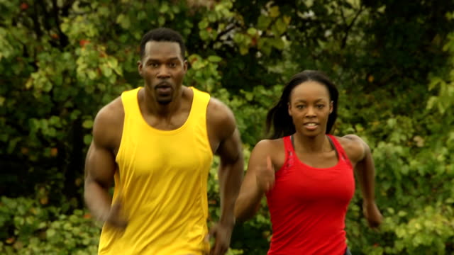 Male and Female Athletes Run Toward Camera
