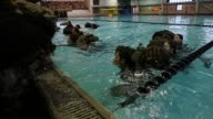 Male and Female Marine recruits haul backpacks while swimming in their uniforms as they are tested to determine their swimming skills during boot...