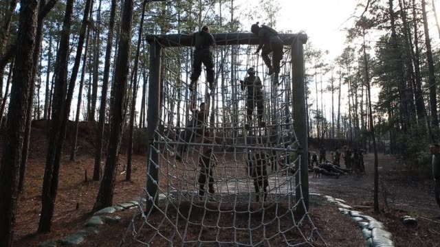 Male and Female Marines climb an obstacle while running the Endurance Course at Marine Combat Training on February 20 2013 at Camp Lejeune North...
