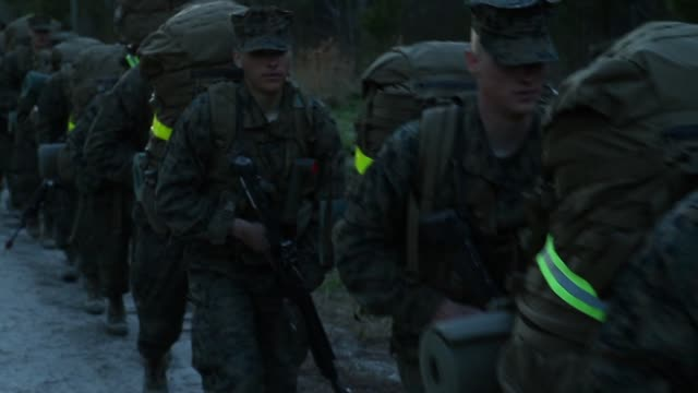 Male and female Marines participate in a 10 kilometer hike carrying 55 pound packs at Marine Combat Training on February 22 2013 at Camp Lejeune...