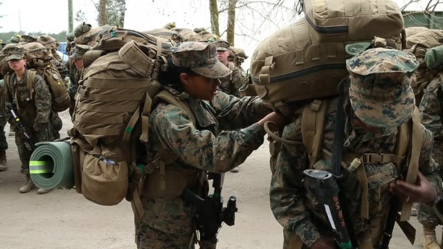 Male and female Marines prepare to head out for a 10 kilometer hike carrying 55 pound packs at Marine Combat Training on February 22 2013 at Camp...