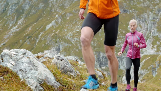 SLO MO Male and female runner ascending the mountain on a rocky grass covered slope