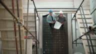 LD Male architect and male project manager discussing construction progress standing at the bottom of the scaffold staircase at the construction site