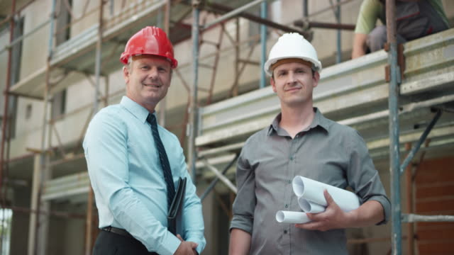 Male architect and project manager shaking hands at the construction site