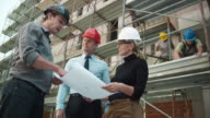 Male architect, female engineer and the project manager talking at the construction site while holding the plans in their hands