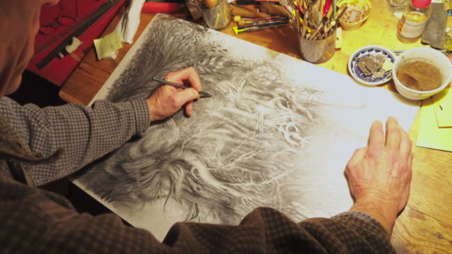 Male artist's hand sketching black and white picture