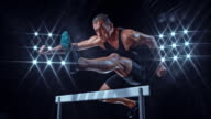 SLO MO DS Male athlete in black outfit doing a hurdle jump at night