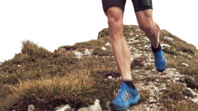 Male athlete running a marathon a cross a mountain ridge