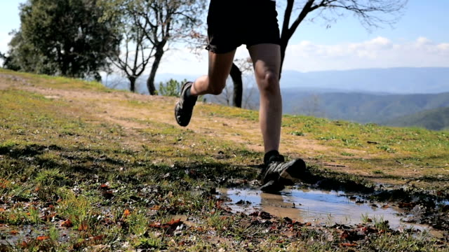 Male athlete running on forest footpath