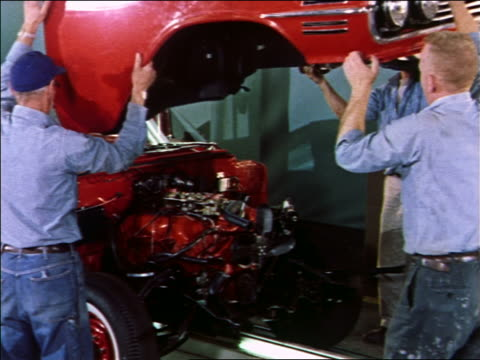 1959 male auto workers attaching red car body to car in assembly line / 1960 Chevy