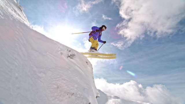 SLO MO Male backcountry skier doing a jump