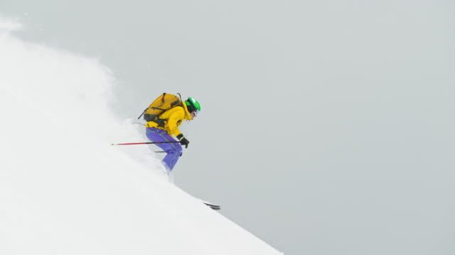 SLO MO Male backcountry skier skiing down mountain slope