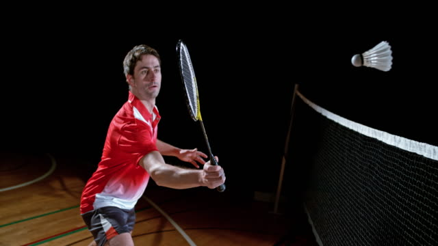 SLO MO Male badminton player in a red shirt hitting the shuttlecock