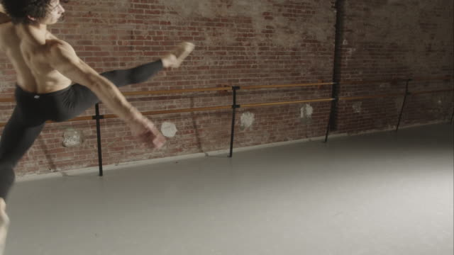 Male ballet dancer practicing jump Tours en l'air in dance studio