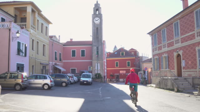 Male bicyclist pedals through village, in sunlight