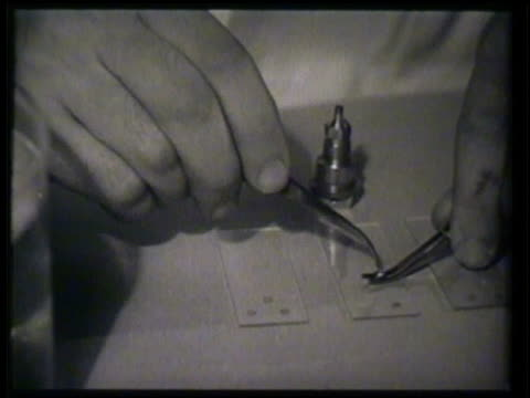 Male biologist scientist in lab working w/ tweezers MCU Using tweezers to insert connect small metal piece VS Operating electron microscope POV of...
