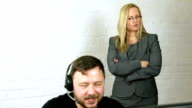 male call center worker at computer with attractive female boss watching over his