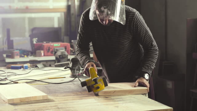 Male carpenter using sander while polishing edges on a piece of wood in a workshop.