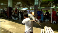 Male carrying dead yellowfin tuna fish on shoulder toward weighing station another man holding tuna on shoulder beyond