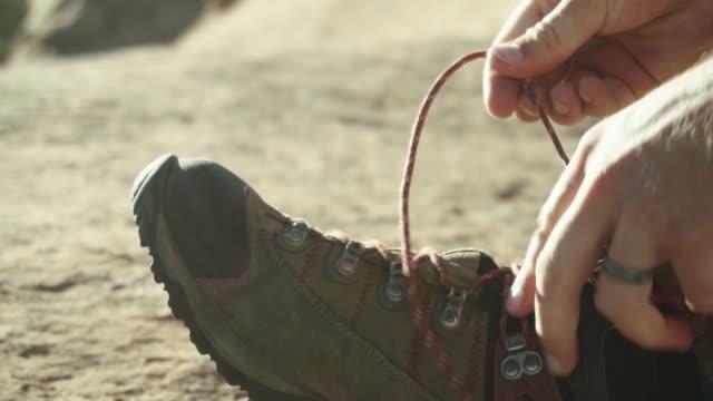 Mannelijke Kaukasische wandelaar banden zijn schoenen