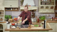 DS Male chef hosting a cooking show talking into the camera while making a dish