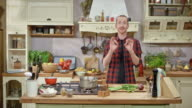 DS Male chef hosting a cooking show talking into the camera while cutting vegetables