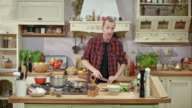 DS Male chef hosting a cooking show, talking to viewers while finely chopping the seasonings on the wooden cutting board