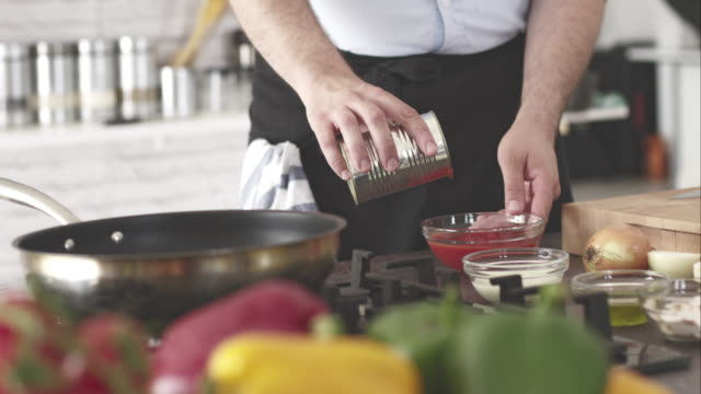 Male chef pouring chopped tomato from the food can