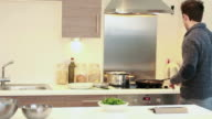 male cooking in kitchen looking at digital tablet