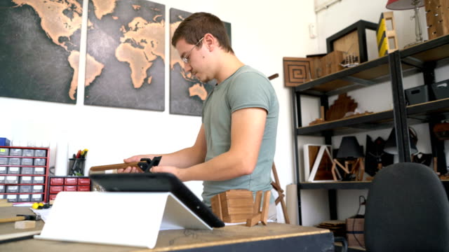 Male crafts-person assembling wooden project and checking on his tablet.