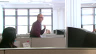 MS, Male customer service representative dancing on desk in office cubicle